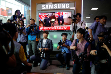 Photographers surround a TV broadcasting a news report on summit between the U.S. and North Korea, in Seoul