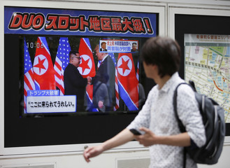 A passerby watches a TV broadcasting a news report on the summit between the U.S. and North Korea, in Tokyo