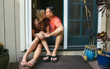 Married middle aged couple sitting in the doorway kissing