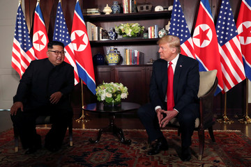 U.S. President Donald Trump sits next to North Korea's leader Kim Jong Un at the Capella Hotel in Singapore