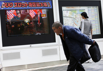 Passersby walks past in front of a TV broadcasting a news report on the summit between the U.S. and North Korea, in Tokyo