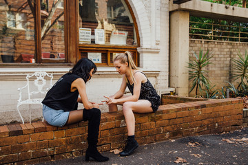 Two Young Women Sit on a brick wall