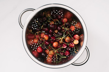 top view of fresh ripe sweet healthy cherries in colander isolated on white