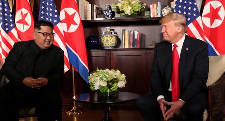 U.S. President Donald Trump sits next to North Korea's leader Kim Jong Un at the Capella Hotel in Singapore