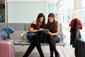 Girls using tablet in waiting area at airport.