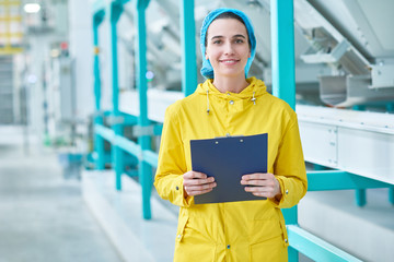 Waist up portrait of cheerful young woman looking at camera standing in clean production workshop of modern plant and holding clipboard, copy space