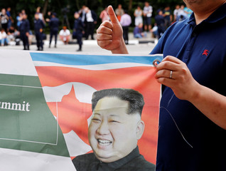A South Korean man flashes a thumbs-up as he holds up a banner in support of the summit between U.S. President Donald Trump and North Korea's leader Kim Jong Un, near the Capella hotel on Sentosa island in Singapore