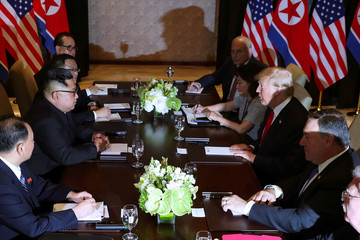 U.S. President Donald Trump speaks with North Korea's leader Kim Jong Un before their meeting in Singapore