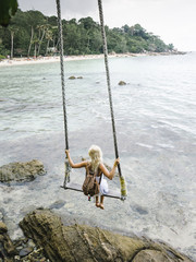 Woman on swings above ocean bay