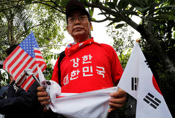A South Korean man holds flags of the U.S. and South Korea as he calls for an improvement in the human rights situation in North Korea near the Capella hotel on Sentosa island in Singapore