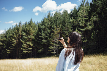 Young woman taking photo with phone in mountains