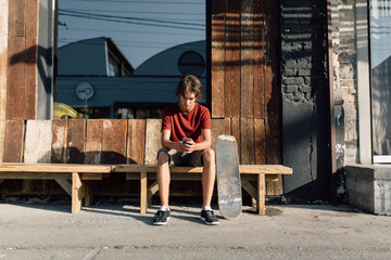 Teenager skater using a smartphone on the street
