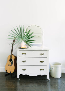 Minimal corner in home with guitar, shelf and plant