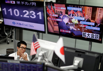 An employee of a foreign exchange trading company works near monitors broadcasting TV news reporting the summit between the U.S. and North Korea in Tokyo