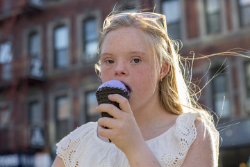 Teenager eating ice cream in an urban environment.