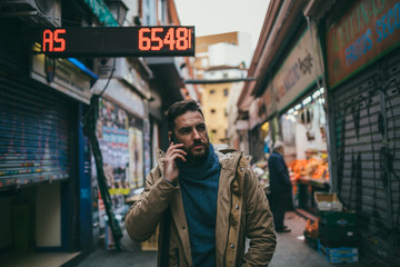 Handsome Bearded Man with Brown Coat talking on the phone