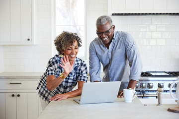 Senior African American couple doing a video chat with family on computer in the kitchen