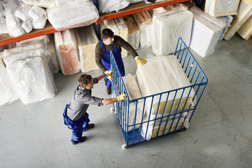 Workers Pushing Trolley With Stacked Mattresses At Sofa Workshop