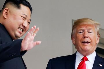 U.S. President Donald Trump and North Korean leader Kim Jong Un react at the Capella Hotel on Sentosa island in Singapore