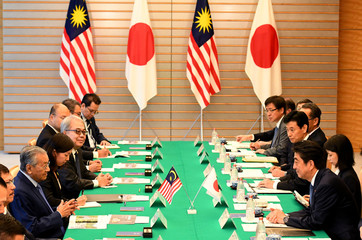 Malaysian Prime Minister Mahathir Mohamad talks with his Japanese counterpart Shinzo Abe during their talks at Abe's official residence in Tokyo