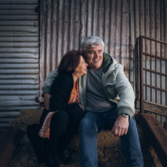 A married senior couple together sitting in a rustic rural setting