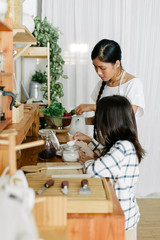 Asian mother and child making tea together in the kitchen