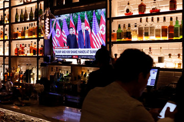 A television screen at the Baro bar broadcasts as U.S. President Donald Trump meets North Korean leader Kim Jong Un in the Korea Town section of Manhattan, New York