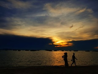 Pattaya, THAILAND - MAY 19, 2018: Silhouette of people having sunset beach in summer vacation as twilight times. Many tourists visit here. View for seascape. Travel concept. Space for text in template
