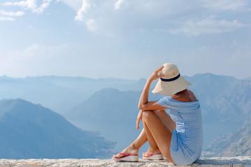 Beautiful girl looks at the bay of Kotor panorama.