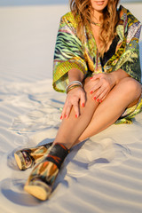 Young caucasian woman wearing green beach robe and having red nails sitting on sand. Concept of beach photo session and summer.