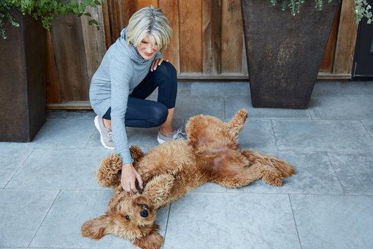 Senior woman petting her dog on patio