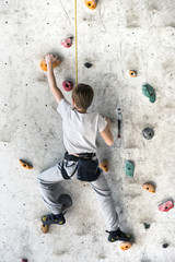 Young free climber training on an indoor climbing wall
