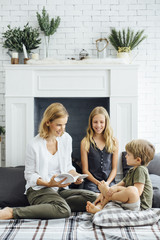 Mother reading book for kids at home