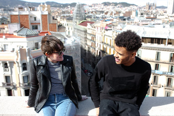 Three young people to look the city on a roof top of a building of Barcelona city
