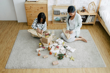 Asian mother and son preparing Christmas present together at home in the living room