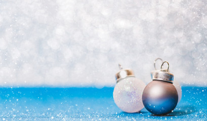 Christmas ball on vivid blue glitter floor and white bokeh blur wall with snow flake falling on ground.Banner with copy space for display of text or design.holiday festive celebration greeting card.
