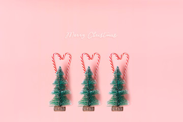 Tree Christmas tree with candy cane hanging on pastel pink wall with white Merry christmas word.Holiday festive celebration greeting card.