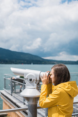 Girl in a yellow raincoat looking through coin-operated telescope at the opposite bank of the lake in Alps