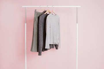 Clothes hanging on a rail on pink background