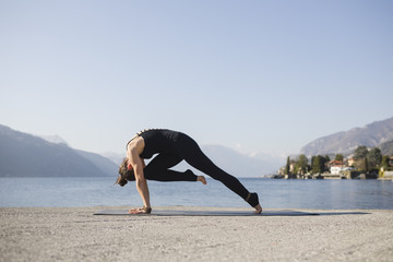 Young woman doing yoga by the lake in a sunny day