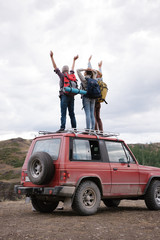 Group posing on car while traveling