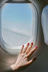 Airplane Window from Inside.  Female Hand with Red Nails.