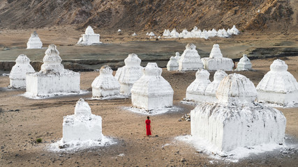Lady in Red Dress Among Tibetan Buddhism Religious Stupas In A Mountain Valley.