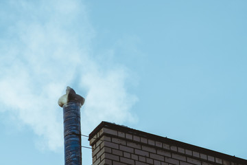 Dove on chimney above bright blue sky in cloud of steam or smoke with copy space. Small pigeon bask on pipe. Beautiful background from clear heaven above roof with silhouette of bird on pipe.