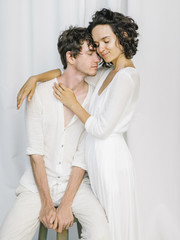 Embracing elegant couple in white