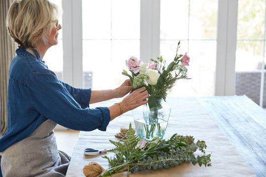 Senior woman arranging flowers in vase on table