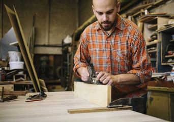 Carpenter working with smoothing bench plane in his workshop