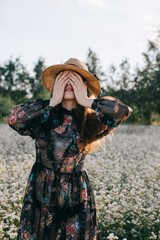 Front view portrait of stylish woman hiding her face with hands outdoors