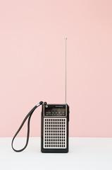 Vintage transistor radio in front of pink background