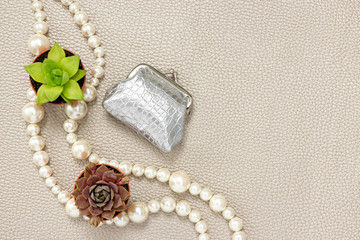 Silver purse, pearl necklace and succulent plants